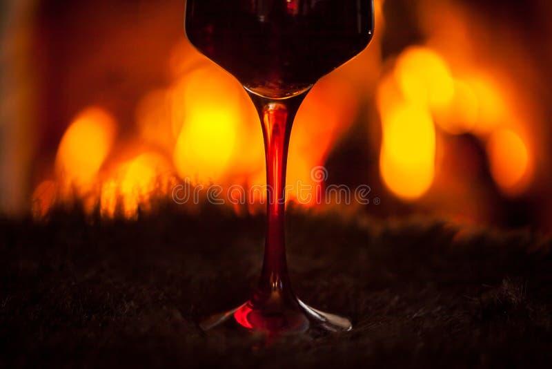 Glas rode wijn tegen comfortabele open haardachtergrond, de wintervaca royalty-vrije stock afbeeldingen