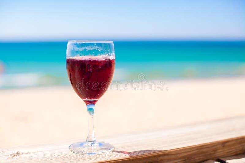 Glas rode wijn tegen het turkooise overzees royalty-vrije stock fotografie