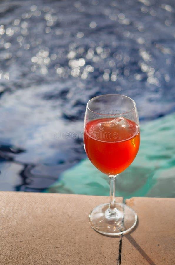 Glas rosafarbener Wein mit einem blauen Hintergrund gegen ein Pool stockfoto