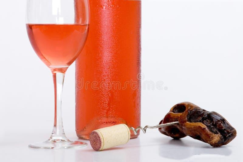 Glas rosafarbener Wein mit Flasche und Korkenzieher lizenzfreie stockbilder
