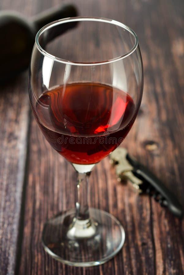 Glas Rotwein über rustikaler, hölzerner strukturierter Tabelle Dunkles Foto lizenzfreie stockbilder