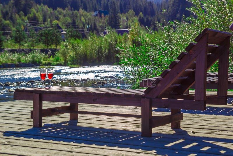 Glas Rotwein auf dem Hintergrund von einem Gebirgsfluss Hölzerner Wagenaufenthaltsraum, Berge, Luxusfeiertag stockfotos