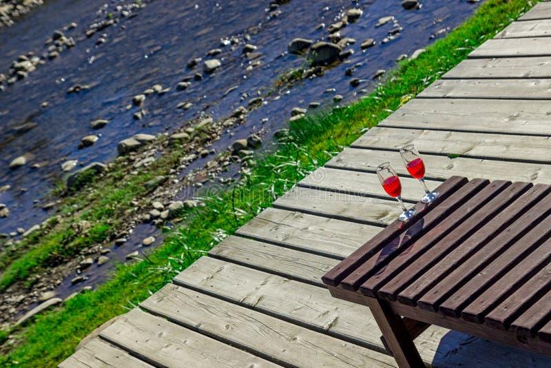 Glas Rotwein auf dem Hintergrund von einem Gebirgsfluss Hölzerner Wagenaufenthaltsraum, Berge, Luxusfeiertag Diagonale stockfotografie