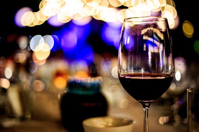 Glas Rotwein auf der Lebensmitteltabelle mit Lichtern Bokeh lizenzfreie stockfotografie
