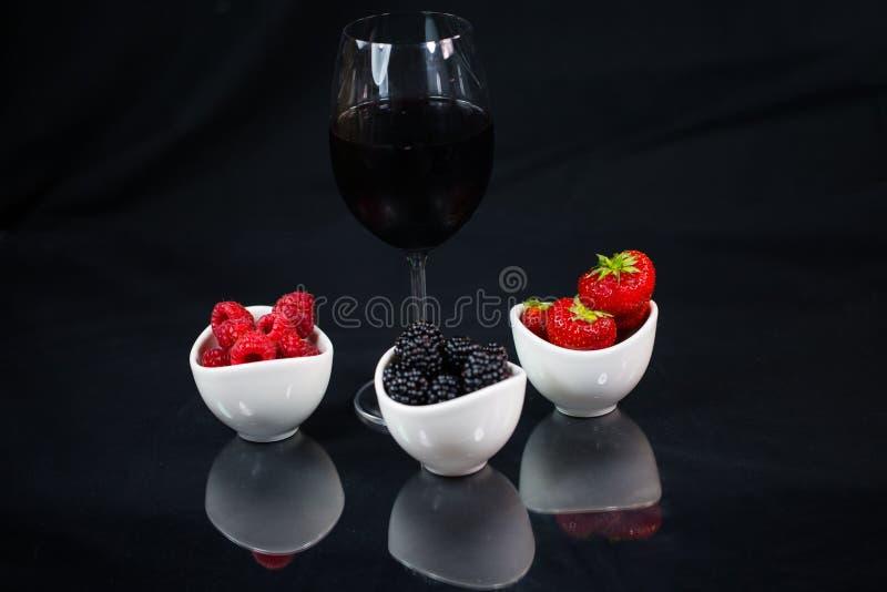 Glas Rotwein auf einem schwarzen Hintergrund mit Erdbeeren, schwarz stockfotografie