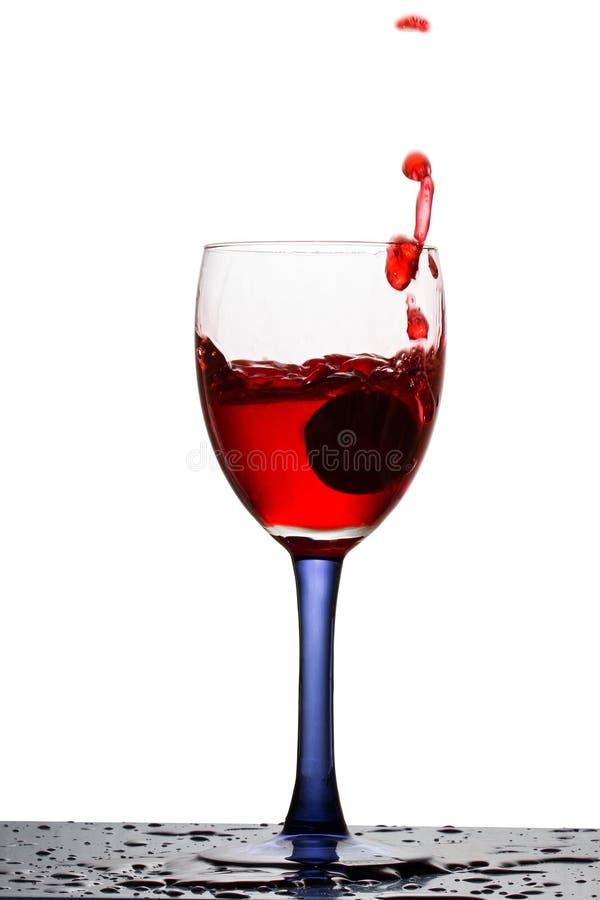 Glas Rotwein mit den hellen Trauben spritzt lizenzfreies stockbild