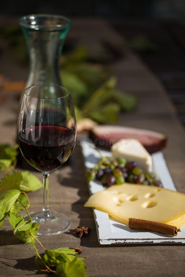 Glas Rotwein, mit Karaffe, Käse und Trauben stockfotografie