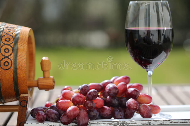 Glas Rotwein mit Trauben auf Holztisch lizenzfreie stockbilder
