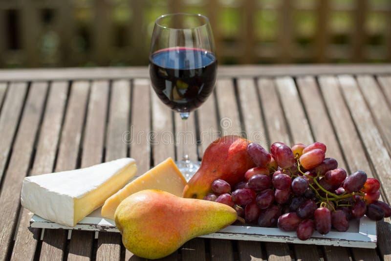 Glas Rotwein mit Trauben auf Holztisch lizenzfreies stockfoto