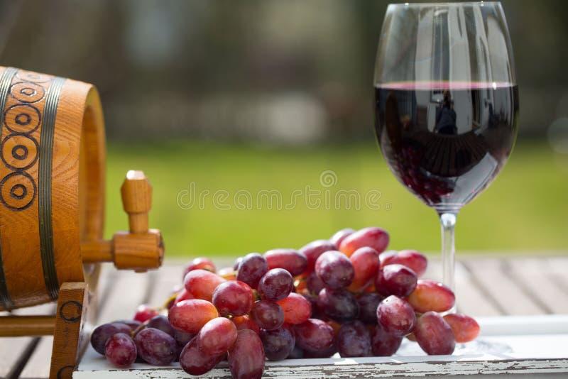 Glas Rotwein mit Trauben auf Holztisch stockbilder