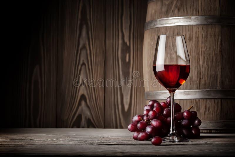 Glas Rotwein mit Trauben und Fass lizenzfreies stockbild