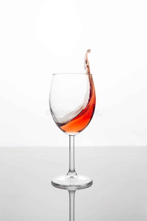 Glas Rotwein mit Welle auf weißem Hintergrund stockbild