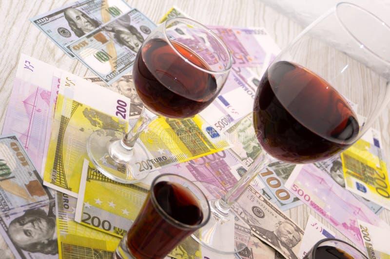 Glas Rotwein und Geld auf einem alten Holztisch Winkelsicht, Fokus auf dem Glas des Rotweins lizenzfreies stockfoto