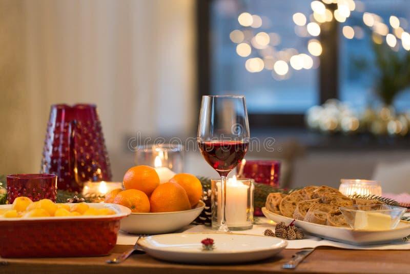 Glas Rotwein und Lebensmittel auf Weihnachtstabelle lizenzfreie stockbilder