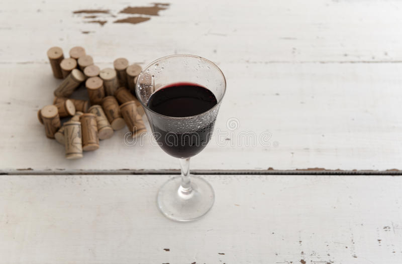 Glas Rotwein und Stapel von Korken stockfotos