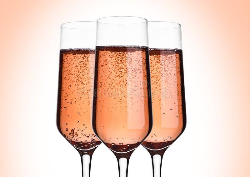 Glas roze roze champagne met bellen op roze stock afbeeldingen