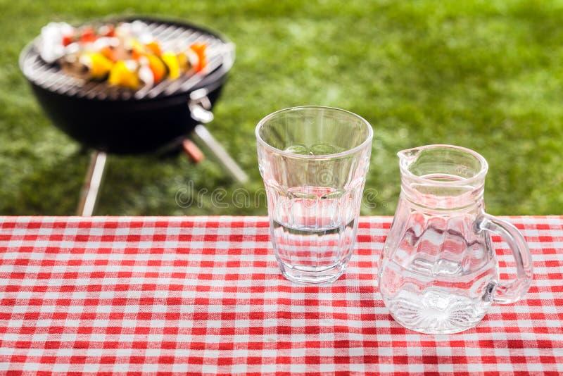 Glas Süßwasser mit einem Krug auf einem Picknicktisch stockfotografie