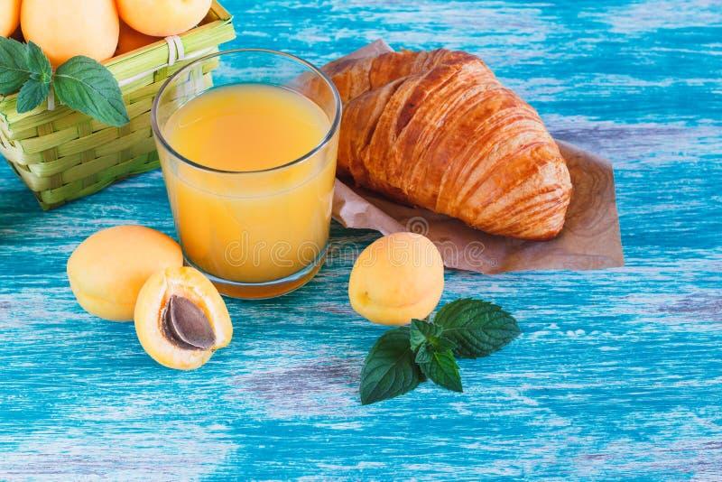 Glas Saft, Hörnchen und Aprikosen lizenzfreie stockfotos