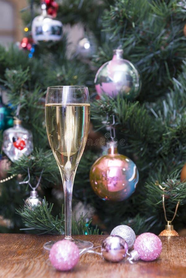 1 Glas Sekt, rosa Weihnachtsbälle auf dem backgroun lizenzfreies stockfoto