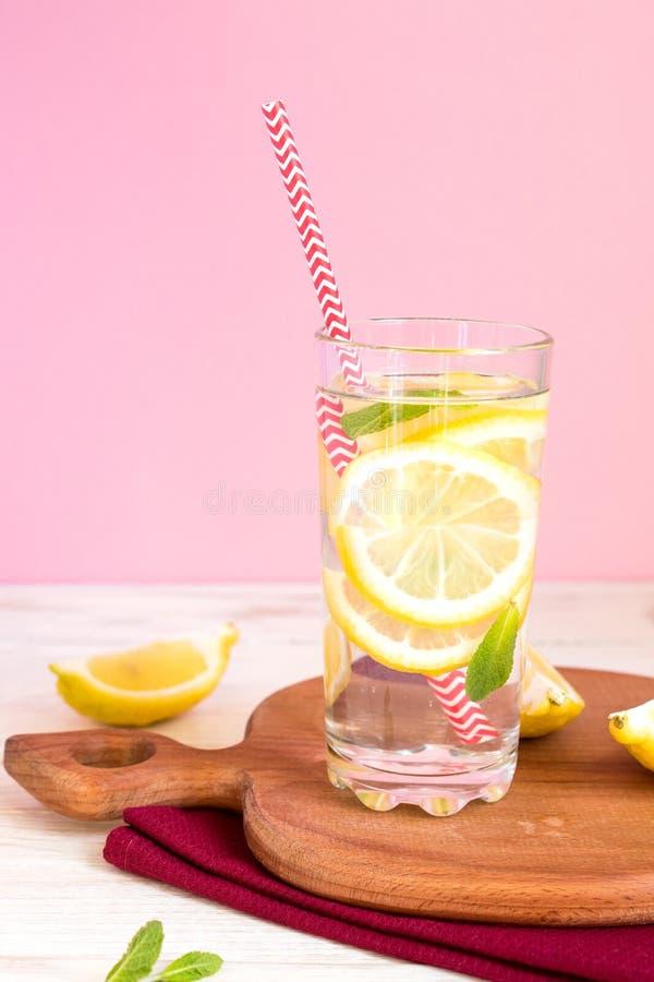 Glas selbst gemachte Limonade mit Zitronen, Minze und rotem Papierstroh auf rosa Hintergrund Auffrischungsgetr?nk des Sommers stockfotos