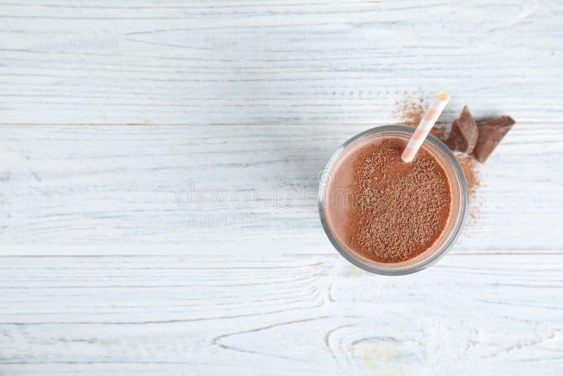 Glas smakelijke chocolademelk op houten achtergrond, hoogste mening met ruimte voor tekst stock foto's