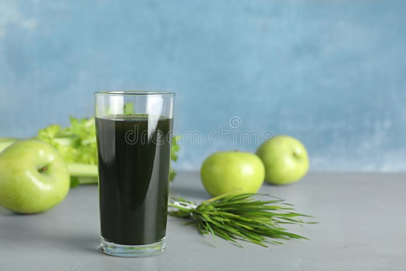 Glas spirulina Getr?nk, Weizengras und ?pfel auf Tabelle gegen Farbhintergrund stockbild