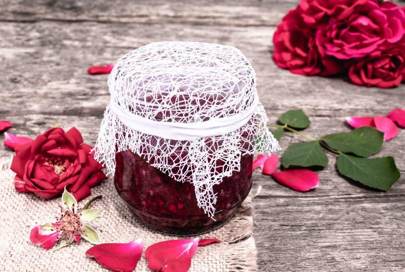 Glas Stau von rosafarbenen Blumenblättern auf einem Holztisch mit Blumen von Rosen Blume Confiture Gesunde Nahrung stockfotografie