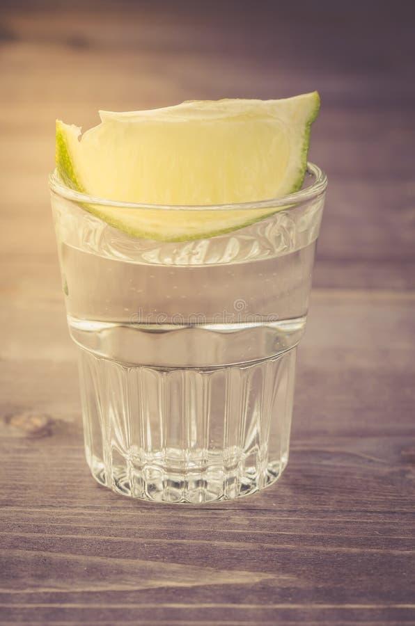 Glas Tequila mit einem Kalk von oben genanntem/vom Glas Tequila mit einem Kalk von oben an einem hölzernen Hintergrund Abschluss  stockbild