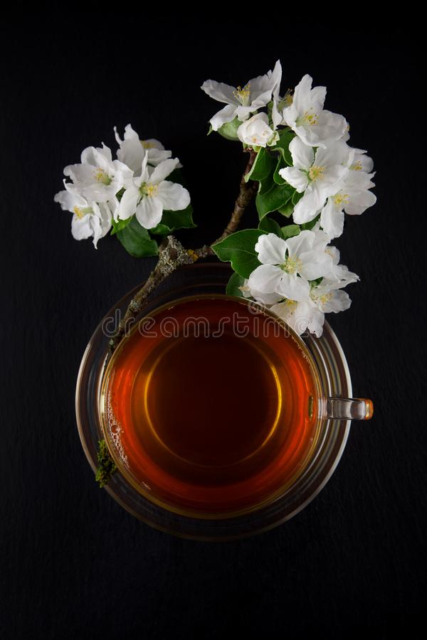 Glas thee met verse rijpe groene die appel met mooie appelbloesem wordt verfraaid op donkere lijst royalty-vrije stock foto's