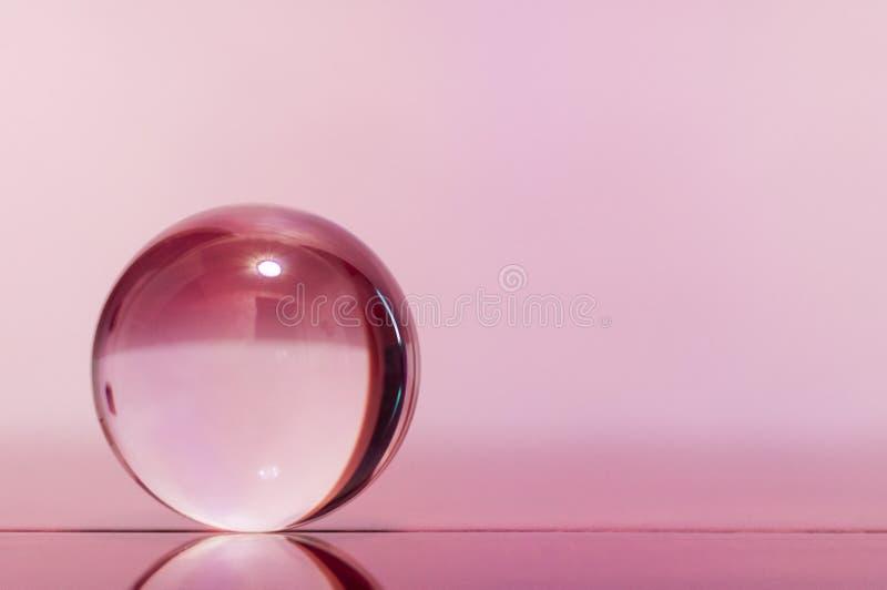 Glas transparante bal op lichtrose oppervlakte als achtergrond en spiegel royalty-vrije stock afbeeldingen