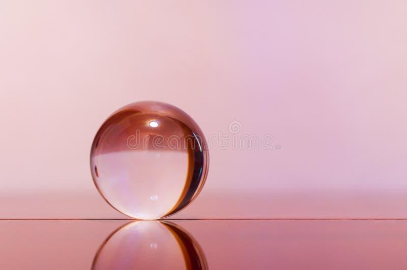 Glas transparante bal op lichtrose oppervlakte als achtergrond en spiegel stock foto