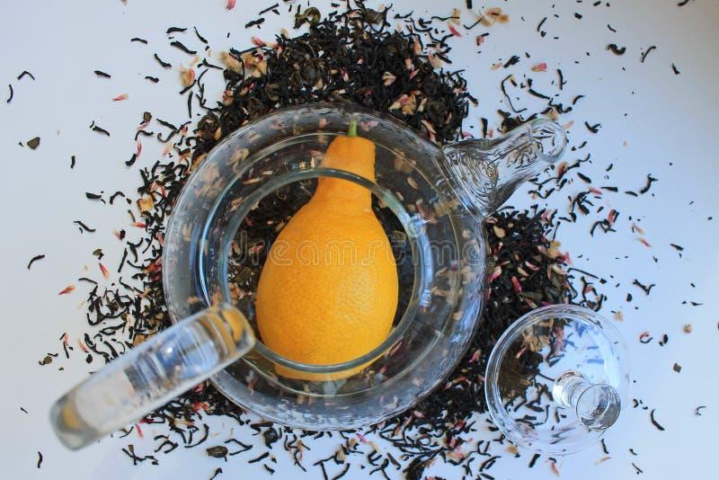 Glas transparante theepot op een witte lijst en verspreid rond zwarte thee met additieven royalty-vrije stock foto