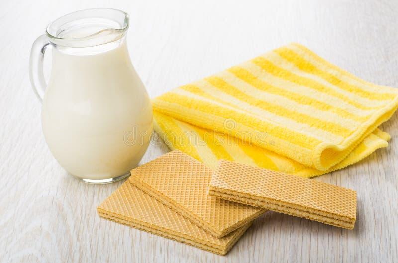 Glas transparante waterkruik met melk, gele servet en wafeltjes stock foto