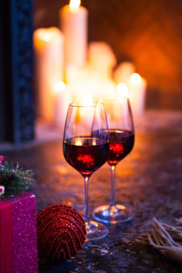 Glas twee met rode wijn op Kerstboom en open haardbackgrou stock foto