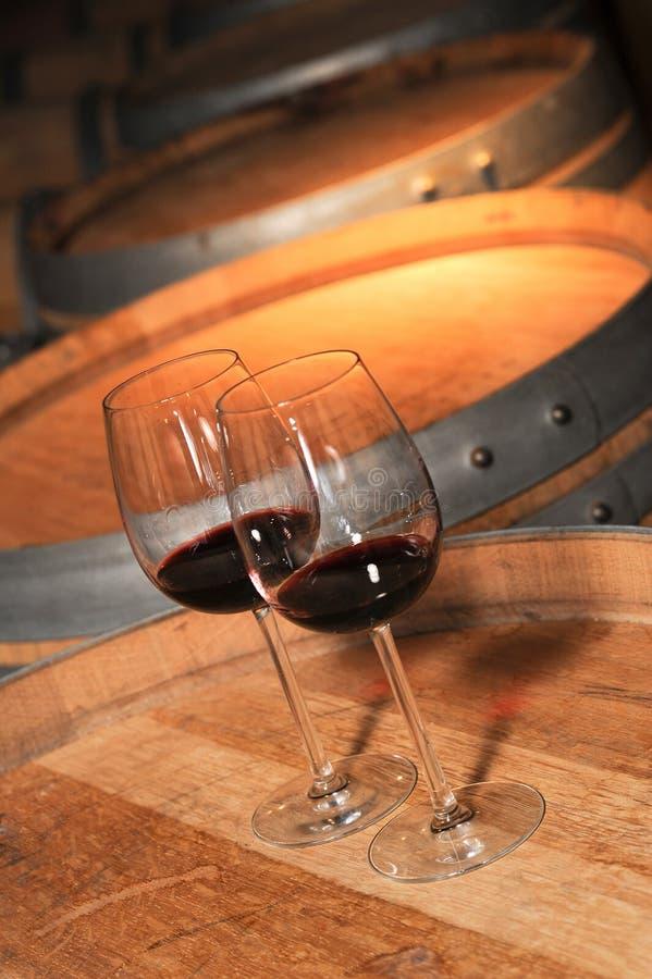 Glas twee van rode wijn en oud vat in kelder royalty-vrije stock afbeeldingen
