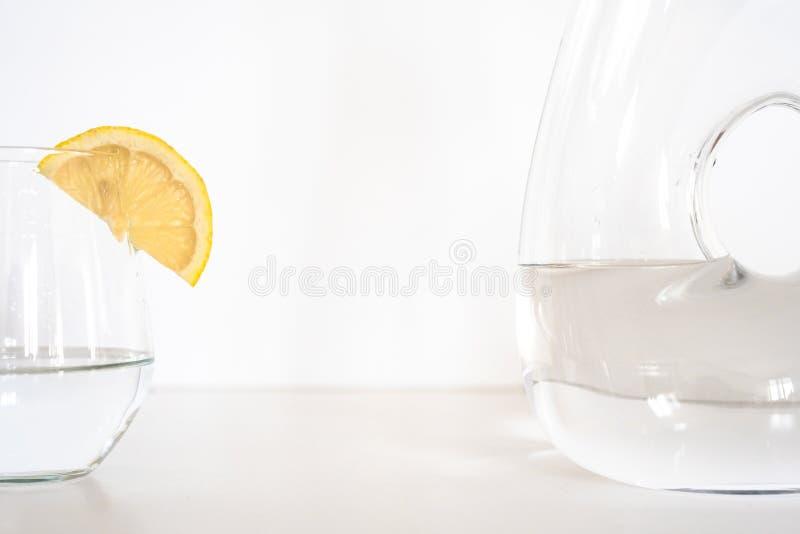 Glas und Flasche Wasser mit Zitronenscheibe stockfoto