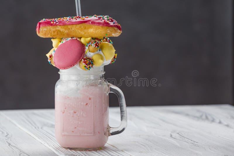 Glas van aardbei smoothie met een broodje stock afbeelding