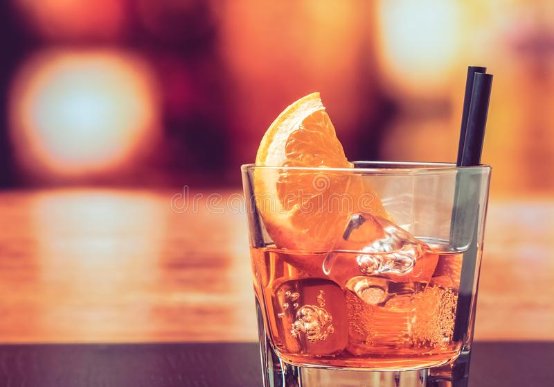 Glas van aperolcocktail van het spritzaperitief met oranje plakken en ijsblokjes op barlijst, uitstekende atmosfeerachtergrond stock fotografie