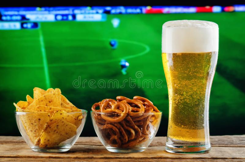 Glas van bier en snack op een achtergrond van TV van het voetbalspel royalty-vrije stock afbeelding