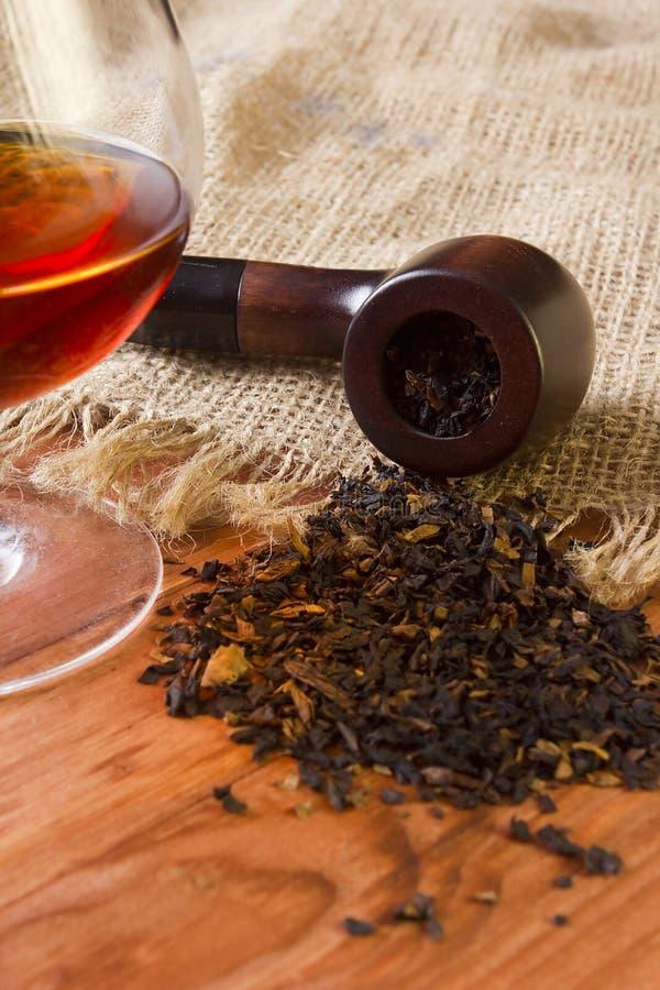 Glas van cognac en pijp met tabak royalty-vrije stock afbeelding