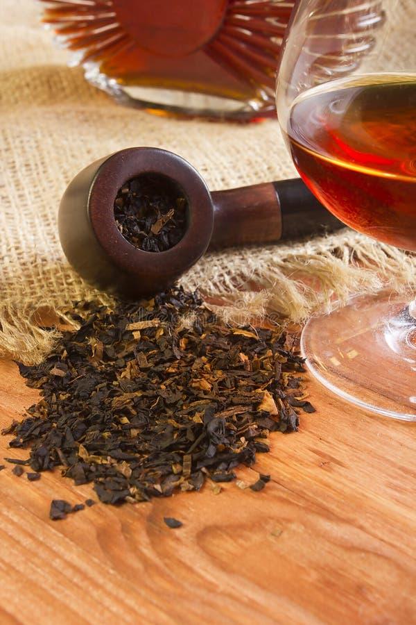 Glas van cognac en pijp met tabak royalty-vrije stock fotografie