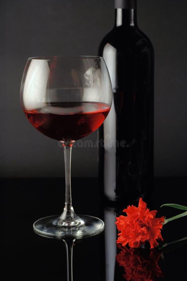 Glas van de wijn, fles en rood nam toe stock afbeelding