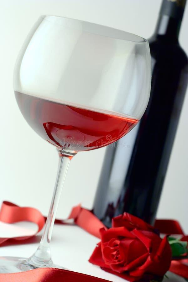 Glas van de wijn, fles en rood nam toe royalty-vrije stock afbeelding