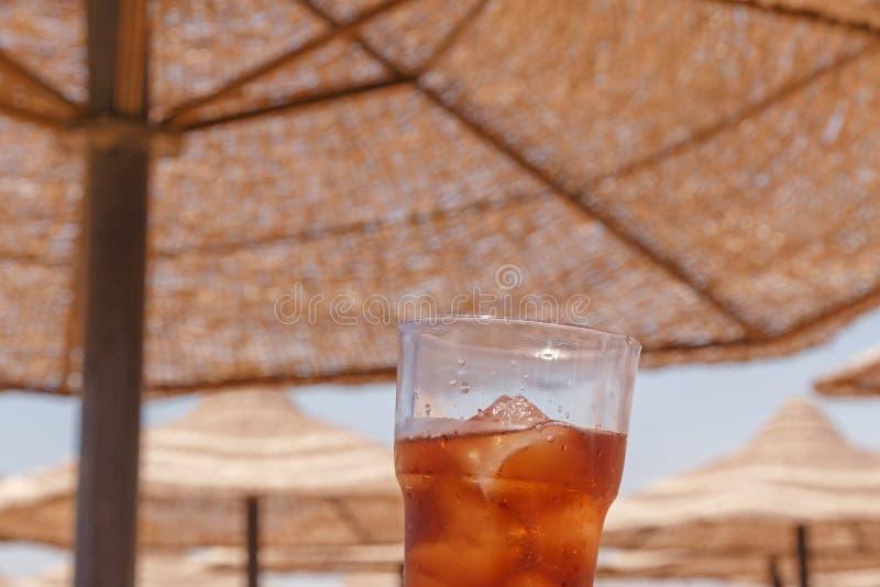 Glas van koude drank tegen zonneschermparaplu's stock foto