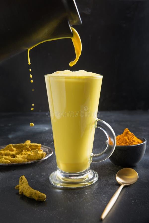 Glas van kurvedische gouden kurkuma latte melk met kurkuma-poeder op zwart Verticaal schot royalty-vrije stock fotografie
