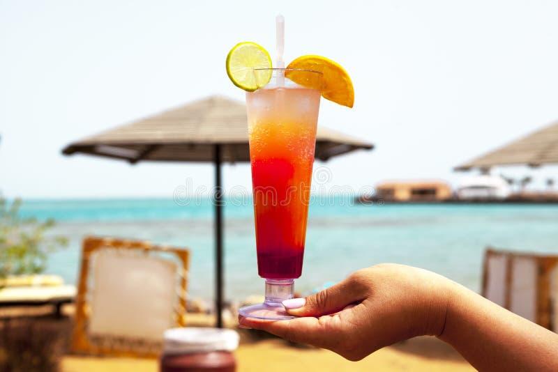 Glas van glas met een cocktail in de hand van een meisje op het strand stock foto