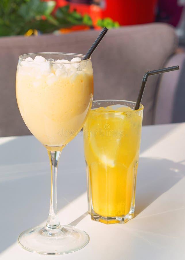 Glas van milkshake met heemst en sinaasappel limonade royalty-vrije stock afbeelding