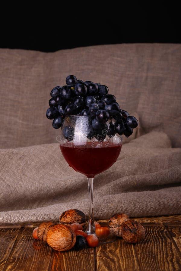 Glas van rode wijn en druif over zwarte royalty-vrije stock foto