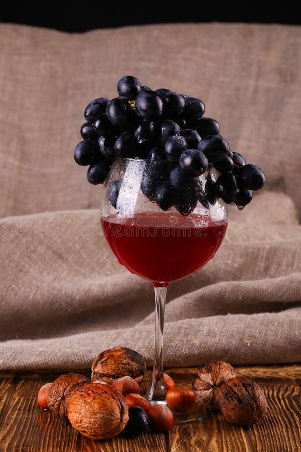 Glas van rode wijn en druif over zwarte stock fotografie