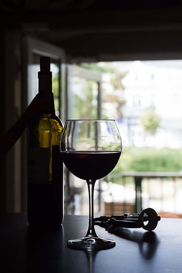 Glas van rode wijn en fles op een barteller op vage deurachtergrond stock foto's